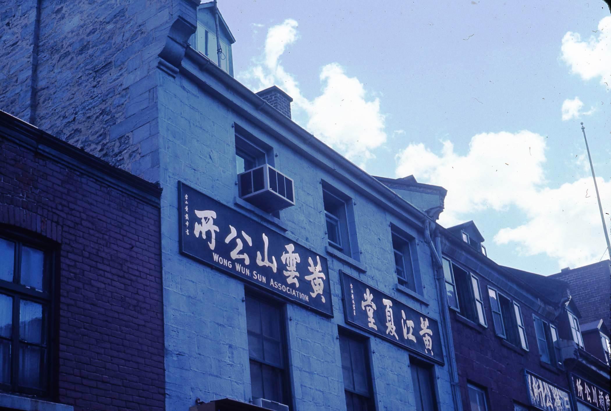 Gros plan sur le haut de façades de maisons du Quartier chinois. Sur celle du centre, deux enseignes en chinois, dont une sur laquelle on peut aussi lire Wong Wun Sun Association.