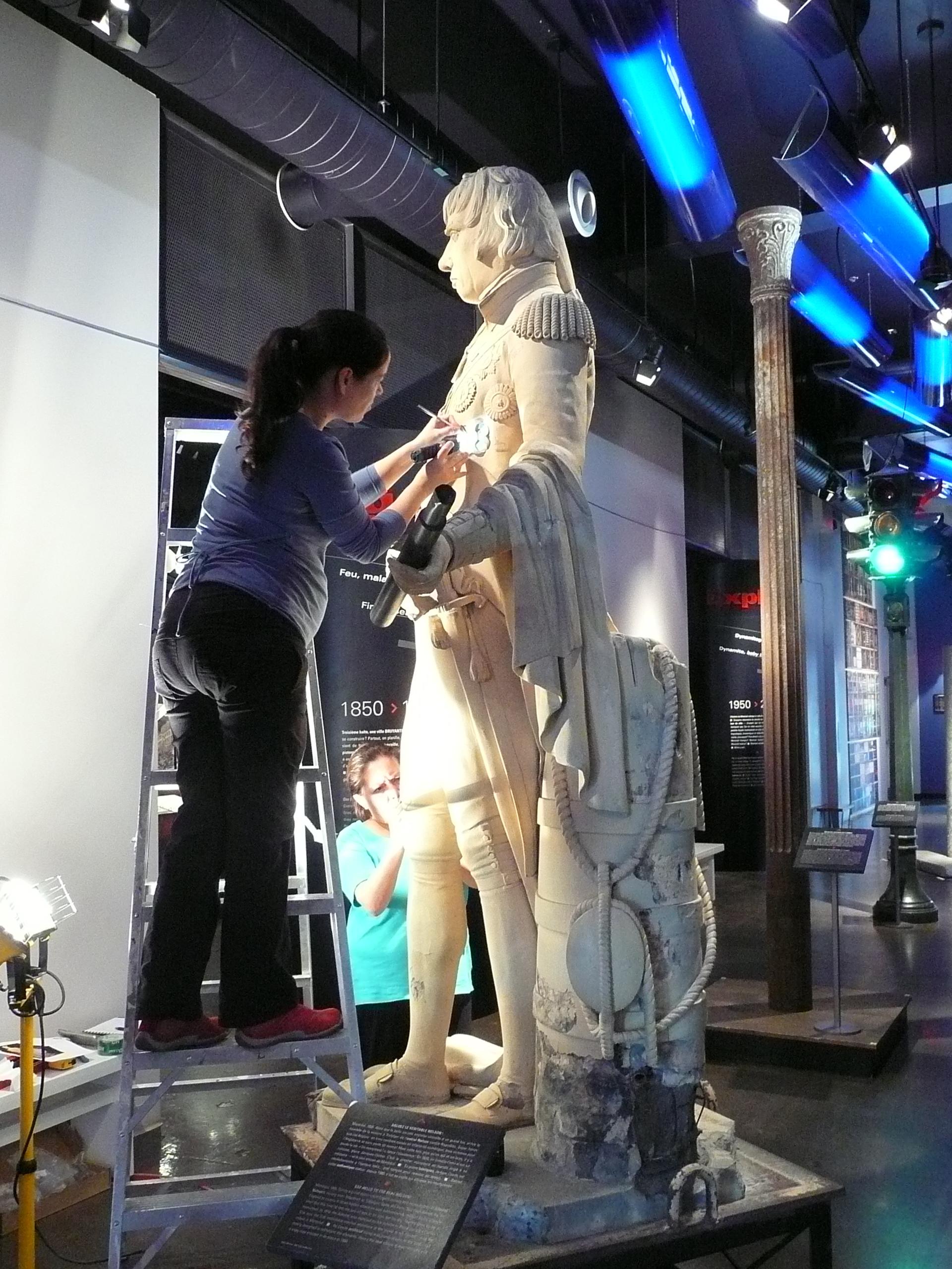 Deux restauratrices du Centre de Conservation du Québec réparent un morceau de la statue de Nelson qui avait été brisé.