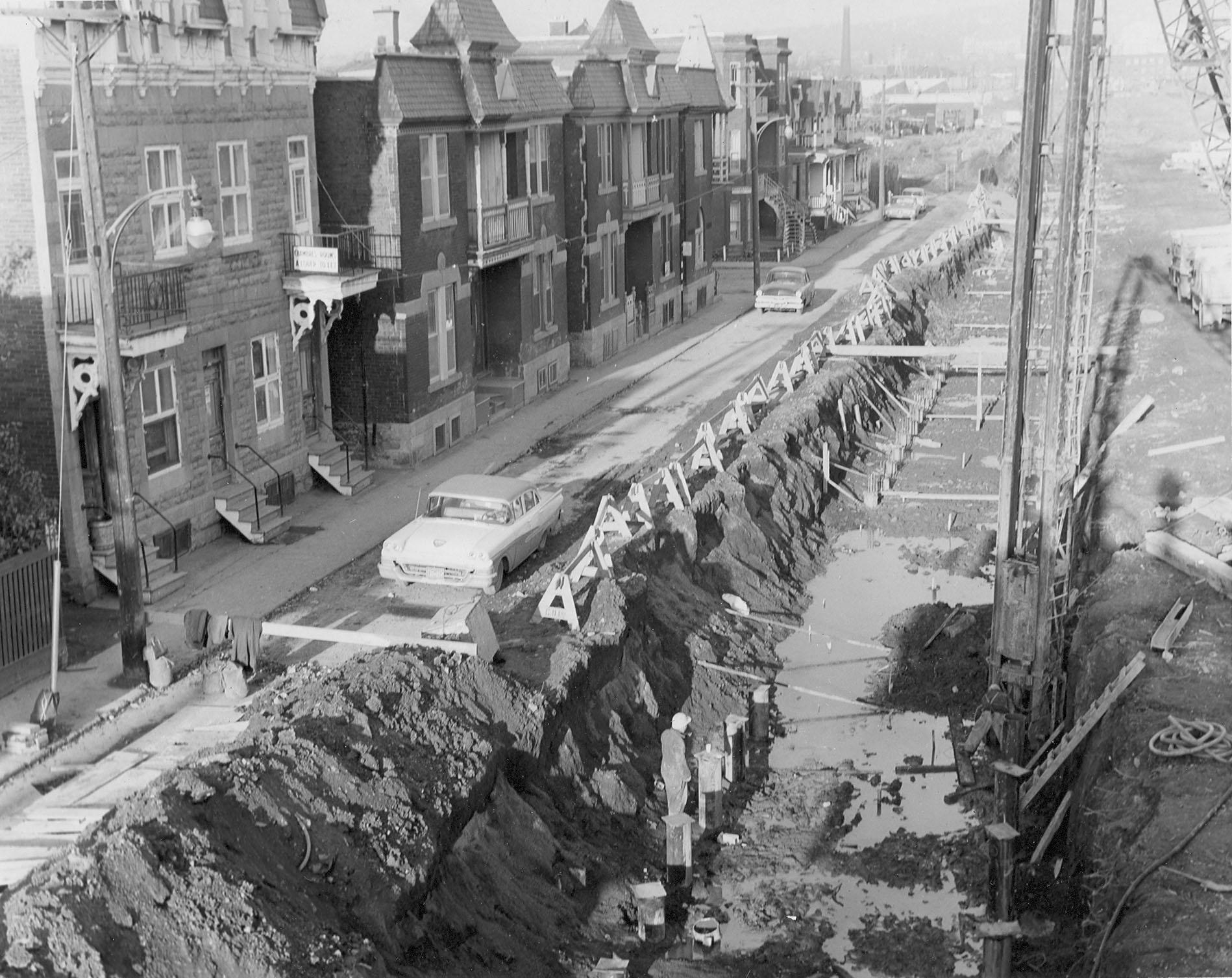 Photo en noir et blanc d'une rangé de maisons du côté gauche d'une rue et du côté droit, travaux de construction montrant une longue tranchée.