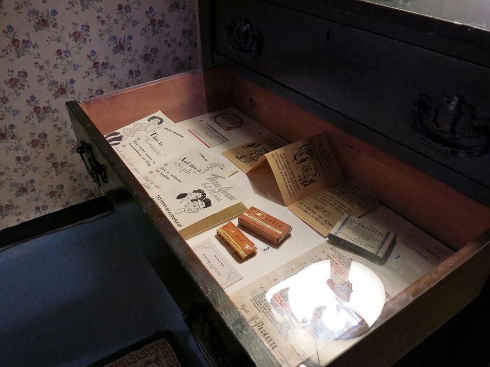 Vitrine qui se trouve dans un tiroir de commode dans une exposition avec différents artefacts dont des sachets de condoms des années 1950 et une trousse de prévention des maladies vénériennes et son livret d'instructions.