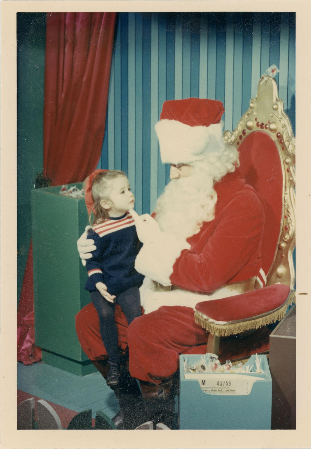 Enfant assise sur les genoux du père Noël au magasin Eaton