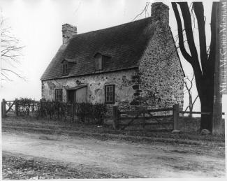 Photo noir et blanc montrant une maison de pierre ancienne le long d'un chemin de terre