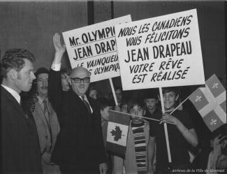 Photographie du maire saluant au centre, entouré d'adultes et de jeunes. Une pancarte affiche « Nous les Canadiens vous félicitons Jean Drapeau votre rêve est réalisé ».
