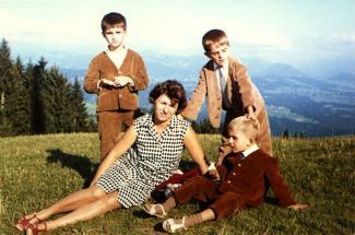 Une femme est assise dans l'herbe. Un jeune garçon est assis à ses côtés. Deux garçons sont debout derrière. On voit les montagnes en arrière-plan