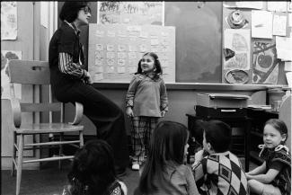 Une élève est debout dos au tableau, à côté de son enseignante. En arrière-plan, quatre élèves.