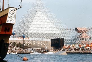 Vue extérieure du lac des Dauphins et de l'attraction nommée Gyrotron de l'Expo 67, avec sa pyramide blanche et le volcan à droite de la photographie. Le Minirail rejoignant les deux structures est également visible.