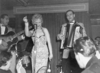Photo en noir et blanc d'une chanteuse et de ses musiciens, un accordéoniste et un guitariste, sur la scène d'un cabaret.
