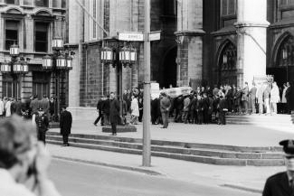Photo en noir et blanc du parvis de l'église Notre-Dame montrant l'arrivée du cercueil de Pierre Laporte.