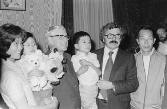 Jacques Couture, ministre de l'immigration sous René Lévesque, en compagnie d'une famille vietnamienne parrainée.