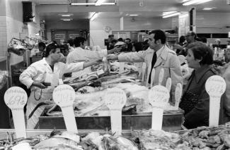 Photo en noir et blanc montrant l'intérieur d'une poissonnerie, avec quelques travailleurs et clients.