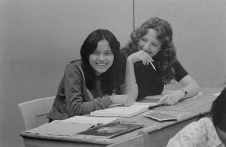 Deux femmes, assises à leurs pupitres souriant. Des livres sont ouverts sur les pupitres.