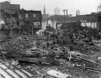 Site de l'écrasement d'un avion dans le quartier Griffintown. Plusieurs maisons sont complètement démolies. Des gens sont sur le site des maisons en ruine.