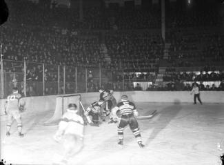 Photo en noir et blanc montrant des joueurs de hockey sur la glace et une foule nombreuse dans les gradins.