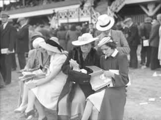 Photo noir et blanc montrant un groupe de femmes s'apprêtant à effectuer des paris sur le terrain de l'hippodrome Mont-Royal. Nous apercevons à l'arrière-plan une partie des installations du champ de course.