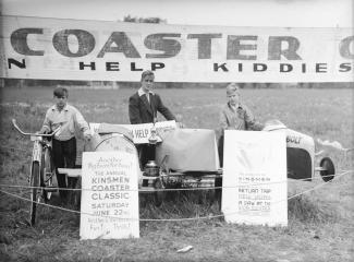 Trois garçons prennent la pose à côté de leurs boîtes à savon et deux affiches en anglais devant eux annoncent une course.