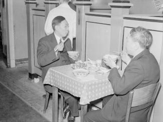 Deux hommes mangent du Chop Suey dans le Quartier chinois.