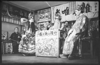 Photo en noir et blanc de six comédiens et musiciens d'origine chinoise sur une scène de théâtre.