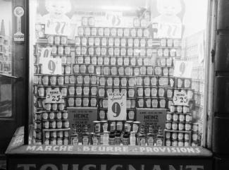 Photographie noir et blanc d'une vitrine avec un étalage de produits en conserve de la marque Heinz. Sur le rebord de la vitrine, il est écrit « Marché à beurre et provisions ».