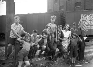La femme de lettres Gabrielle Roy entourée de neuf petits garçons du quartier Saint-Henri à Montréal. Ils sont assis sur une clôture au coin des rues Saint-Augustin et Saint-Ambroise près de la voie ferrée.