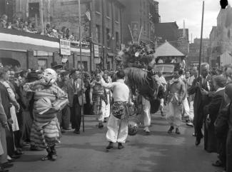 La communauté chinoise célèbre le jour de la Victoire par un défilé dans les rues du Quartier chinois de Montréal. La scène présente la procession du lion et un homme vêtu d'un masque de théâtre chinois.