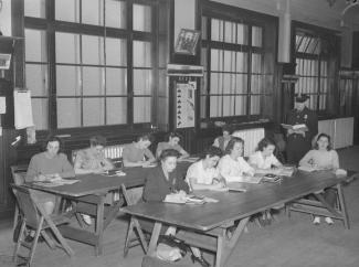 Photographie en noir et blanc de dix femmes policières assises dans une salle de classe avec un policier debout tenant un livre.