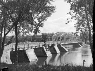 Photo en noir et blanc d'un pont métallique, d'une rive à l'autre.