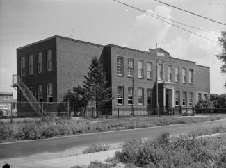 Nous voyons l'extérieur de l'école de briques « Sarah Maxwell Memorial School » située rue Préfontaine à Montréal.