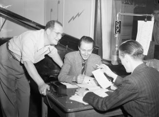 Les animateurs Jacques Normand et Roland Bayeur discutent avec le pianiste accompagnateur Billie Munroe dans un studio d'enregistrement de la station radio CKVL à Montréal.