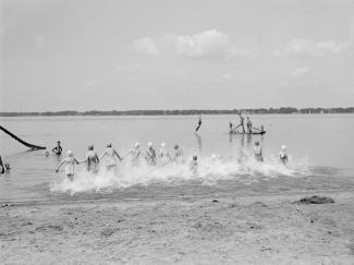 Des enfants se tenant par la main entrent dans l'eau sur une plage
