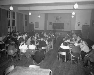 Une cinquantaine de personnes sont réunies dans une salle et regroupées autour de tables.