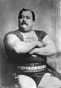 Photographie en noir et blanc d'un homme portant un costume de lutteur sur lequel il est écrit « Canada » au niveau du torse. L'homme a les bras croisés et porte une moustache.