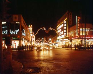 Photo couleur montrant la Plaza Saint-Hubert décorée pour le temps des fêtes en soirée avec les enseignes lumineuses, des voitures et des gens au coin de la rue sur le trottoir.