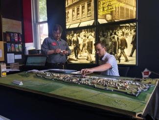 Deux employés du Centre d'histoire travaillent sur la maquette de Montréal en 1745