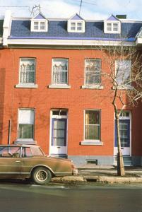 Façade d'une maison sur la rue Dézéry avec une voiture en avant-plan