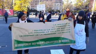 Deux femmes tiennent une bannière du Regroupement des cuisines collectives du Québec lors d'un événement