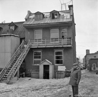 Un homme tient une pancarte devant l'arrière d'une maison l'identifiant pour l'expropriation