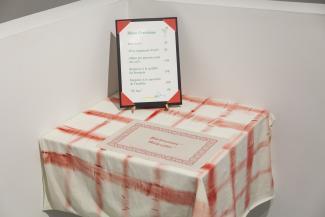 Photo d'une oeuvre artistique montrant une table, un napperon et un menu intitulé « Menu d'exotisme ».