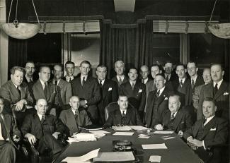 Photo en noir et blanc d'une assemblée d'hommes en complet prenant la pose derrière une table. Six sont assis et dix-sept sont debout.