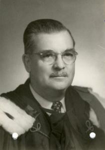 Photo en plan buste d'un homme portant des lunettes et une moustanche.