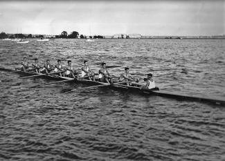 Photo en noir et blanc d'un bateau d'aviron à huit rameurs et un barreur leur faisant face avec un porte-voix. En arrière plan, les arches d'un pont ferroviaire.
