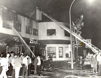 Pompiers, policiers et foule devant le Blue Bird incendié