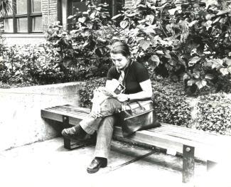 Photo noir et blanc d'une jeune femme lisant, assise sur un banc à l'extérieur d'un édifice.
