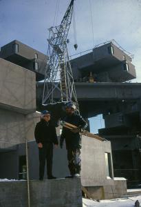Deux ouvriers et une grue sur le chantier de construction du complexe Habitat 67.