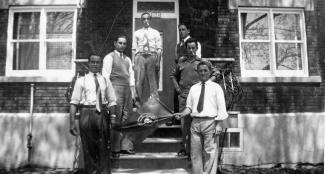 Six Açoriens posent devant une maison en tenant un drapeau.