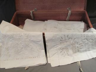 Valise ouverte d'une immigrante italienne contenant quatre couvre-oreillers et trois draps en lin.