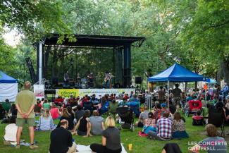 Un groupe de musiciens sur une scène extérieure joue devant un public assis sur la pelouse et des chaises.