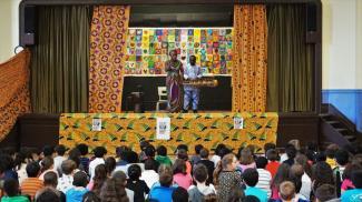 Spectacle de contes africains dans une école primaire. Deux artistes sont sur scène et les enfants sont assis par terre face à la scène.
