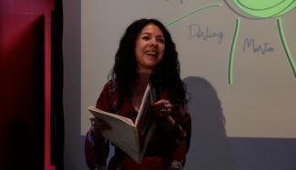 Une femme tenant un cahier devant un écran