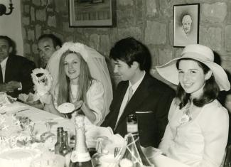 Des mariés, deux hommes à leur gauche et une jeune fille à leur droite, assis à une table