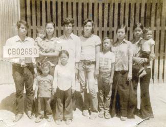 Photo en noir et blanc d'un groupe d'adultes et d'enfants cambodgiens. Un adulte tient une pancarte avec un numéro.